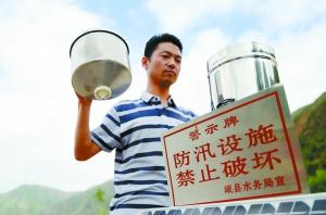 7月20日,在岷县禾驮乡哈地哈村,水务工作人员在检查自动雨量监测站设备。新华社照片