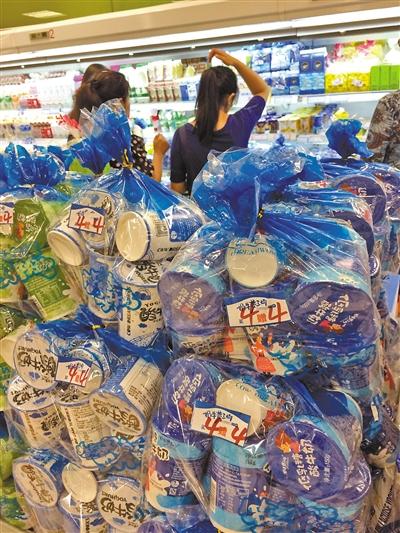 解放碑一家超市里,酸奶促销区的酸奶堆得半人高。