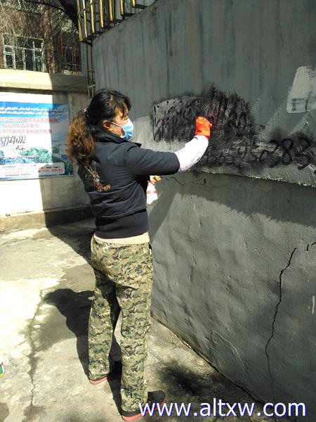 新疆阿勒泰市金山路社区志愿者进社区清理小广告