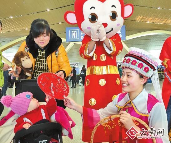 2月13日,昆明长水国际机场工作人员身着民族服装为即将离开的游客送上礼物和节日祝福。记者 周灿 陈飞 摄